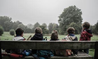 Five children sitting on a bench